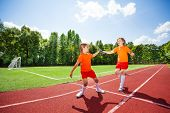 image of relay  - Running girl with one relay baton handing it to other girl during relay race - JPG