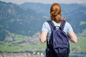 foto of bavarian alps  - Back view of a young woman carrying a backpack on a hiking trip in the Bavarian Alps - JPG