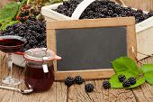 stock photo of blackberries  - Blank slate blackboard in front of ripe blackberries blackberry liqueur and a jar blackberry jelly on a rustic wooden table - JPG