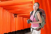 foto of inari  - Happy smiling Asian young female backpacker with camera in Fushimi Inari Taisha - JPG