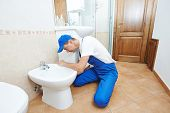 stock photo of plumber  - plumber worker working with spanner at sanitary washbasin installation system - JPG