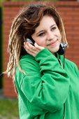 image of dreadlocks  - Smiling girl with dreadlocks listening to music outdoors - JPG