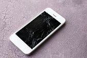 foto of wrecking  - Modern mobile phone with broken screen on wooden background - JPG