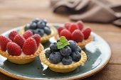 stock photo of tarts  - Delicious mini tart with fresh raspberries and blueberries on wooden background - JPG
