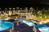 stock photo of tourist-spot  - night hotel with the pool and trees the excellent vacation spot of tourists - JPG
