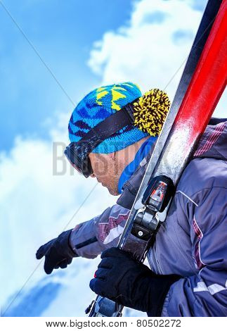 Handsome ski trainer shows the way for the descent from the mountain covered with snow, luxury ski resort, winter vacation concept