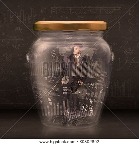 Businessman traped in jar with graph chart symbols concept on background
