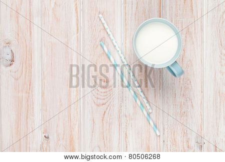 Cup of milk and drinking straws on white wooden table with copy space
