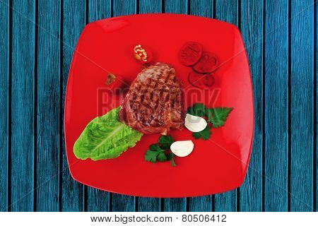 meat savory : beef grilled and garnished with green lettuce and red chili hot pepper on red plate isolated over white background