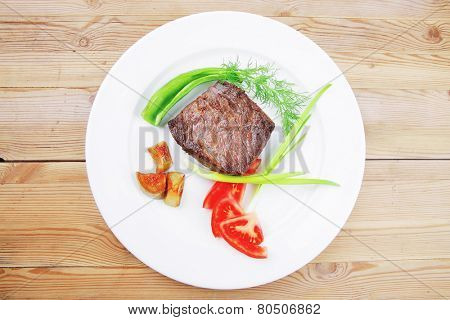 meat food : roast beef fillet mignon served on white plate with apples dill and tomatoes over wooden table