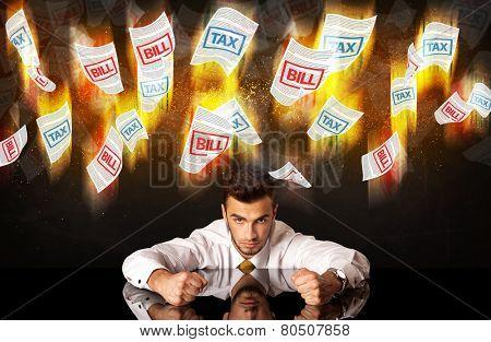 Depressed businessman sitting under falling papers