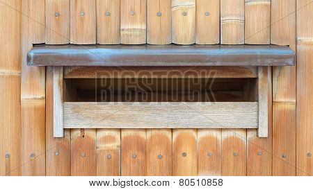 Wood mail box on traditional bamboo wall background