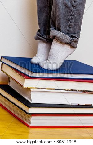 child standing on a pile of books, symbolizing education, reading, learning support