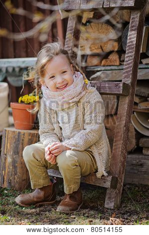 cute happy child girl with pigtails sitting on wood shed with dandelions in country spring garden