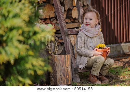 cute happy child girl with pigtails sitting on wood shed with dandelions in spring garden