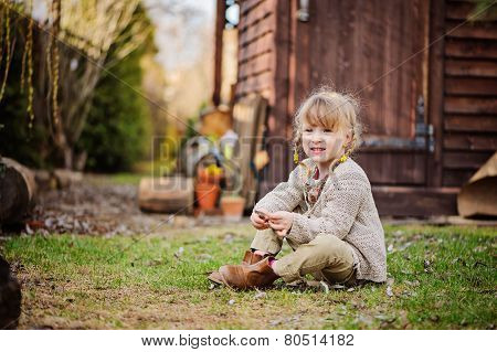 adorable child girl with pigtails plays in country spring garden