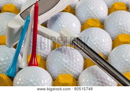 White Golf Balls In The Yellow Box And Golf Putter