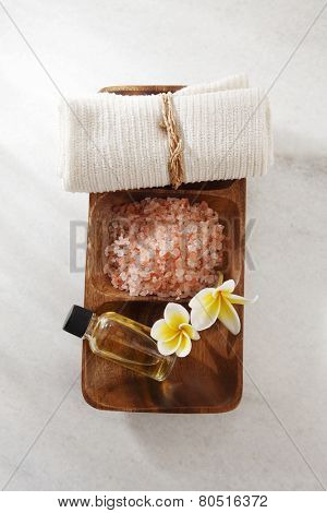 frangipani flower,salt,massage oil and towel in a wooden bowl