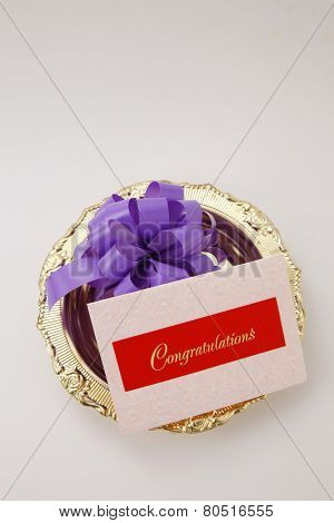 top view purple ribbon bow and a congraturation card