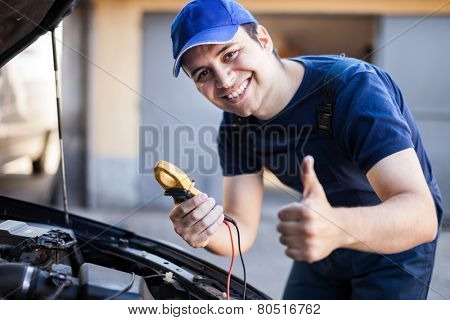 Smiling mechanic troubleshooting a car engine