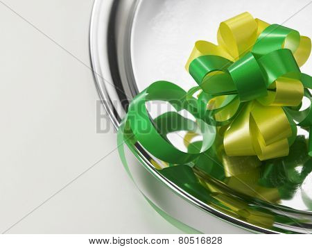 green yellow ribbon bows on the silver plate