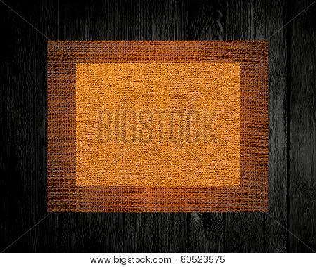 Burlap rustic canvas textured on dark wood background