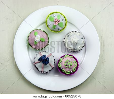 Five Decorated Muffins On White Dish