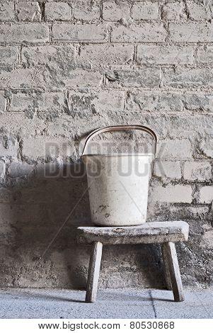 grunge wall, white plastic bucket