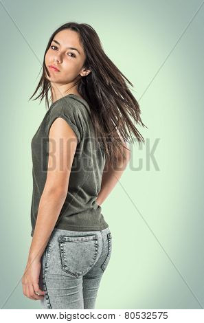 Young pretty teenager girl turning her head and looking back