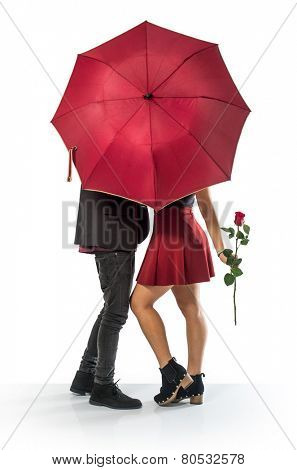 Couple of sweethearts kissing behind a red umbrella