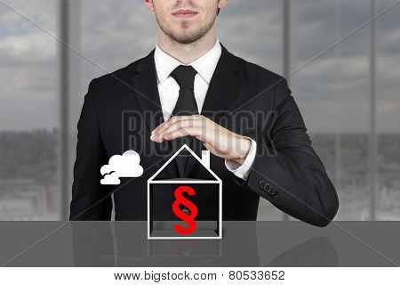 Businessman Holding Protective Hand Above Building Paragraph Symbol
