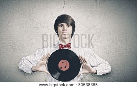 Young handsome man dj holding disco plate