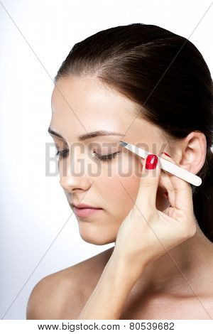 Attractive young woman plucking eyebrows