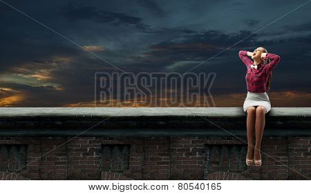 Young woman sitting on roof and covering ears with hands