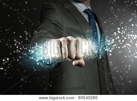 Close up of businessman grasping star dust in fist