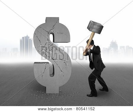 Businessman Holding Hammer Hitting Cracked Dollar Sign With Cityscape Background