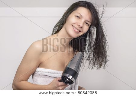 Attractive Woman In A Towel Blow Drying Her Hair
