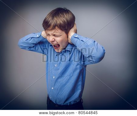 teenager boy closed ears with his hands gray background