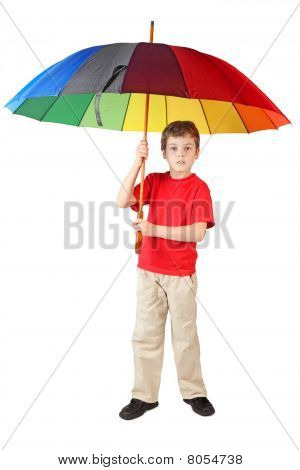 Little Boy In Red Shirt With Big Multicolored Umbrella Standing On White Looking At Camera