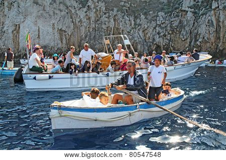 Tourists In Small Boats Waiting To Enter The Blue Grotto On Capri