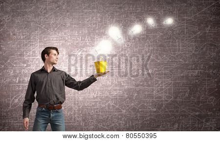Young man in casual and light bulbs from bucket
