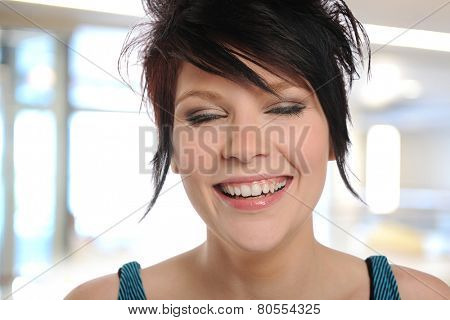 Close up of a young woman smiling inside an office building