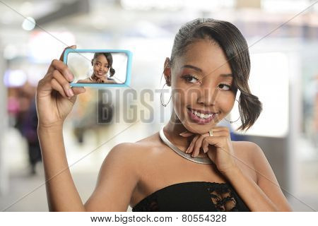 Young black woman taking a selfie inside an airport