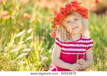 Beautiful little girl in a field of blooming poppies.