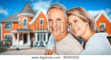 Happy couple near new home. Residential construction background.