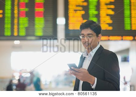 Asian Indian Business man checking on smartphone, doing online web check in at the airport .