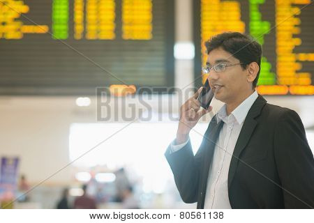 Asian Indian Business man on the phone during his business travel, at the airport .