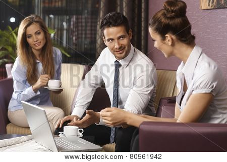 Business partners talking and working by coffee in hotel lobby or bar, using laptop computer, smiling.