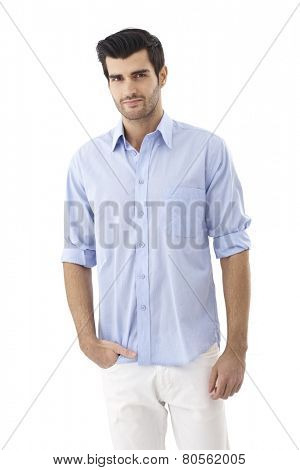 Portrait of casual young man in shirt, standing with hand in pocket, looking at camera.