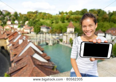 Smartphone screen - Woman showing app in Bern Switzerland, Europe. Girl holding blank empty smart phone screen on travel with copy space. Happy smiling Asian girl in Swiss Berne. Focus on screen